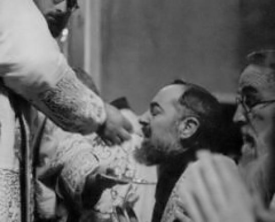 Saint Padre Pio commmuniant à genoux