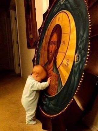 Pieux Bébé touchant une icône de Jésus